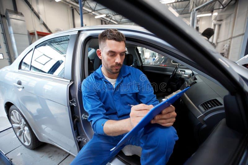 Hombre del mecánico de automóviles con el tablero en el taller del coche foto de archivo libre de regalías