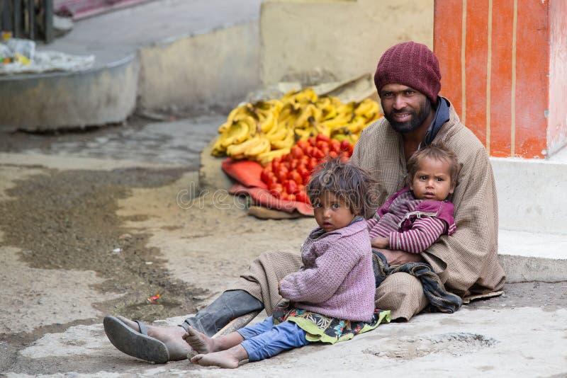 Hombre del mendigo con los niños que piden en la calle en Leh, Ladakh La India imagenes de archivo
