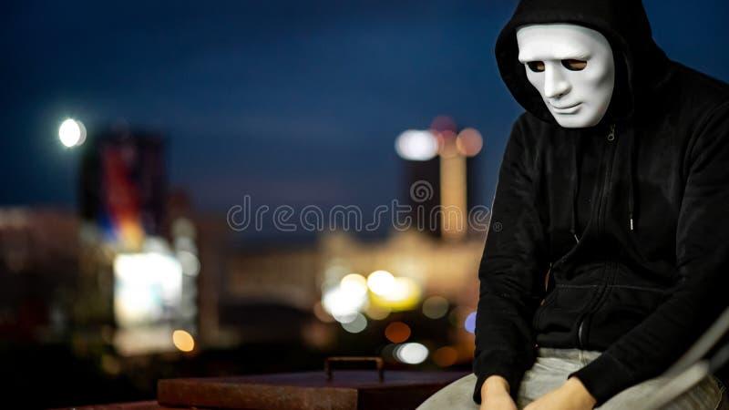 Hombre del misterio en la máscara blanca que se sienta en tejado fotografía de archivo
