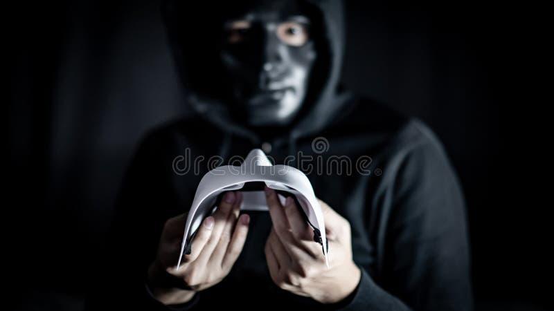 Hombre del misterio en la máscara negra que lleva a cabo la máscara blanca fotos de archivo libres de regalías