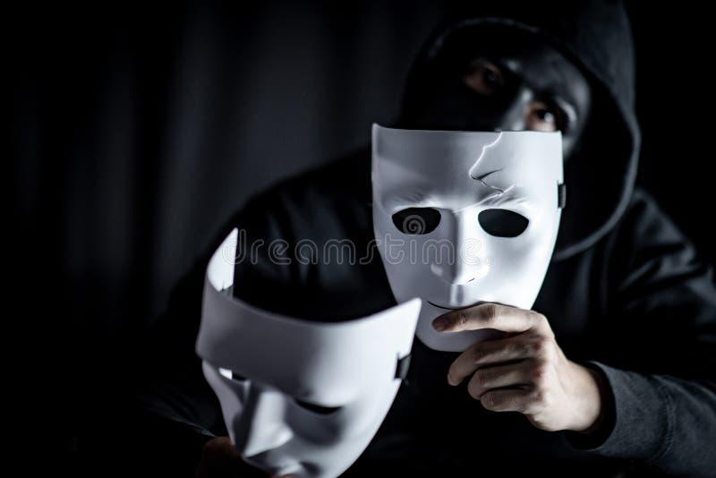 Hombre del misterio en la máscara negra que lleva a cabo las máscaras blancas imágenes de archivo libres de regalías