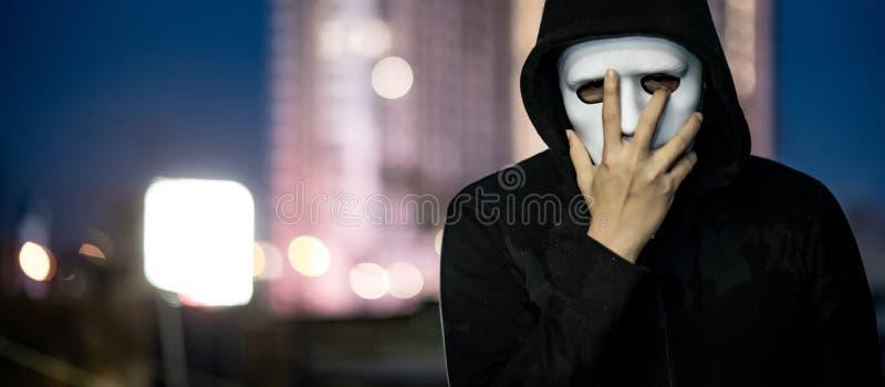 Hombre del misterio en la situación blanca de la máscara en tejado imagenes de archivo