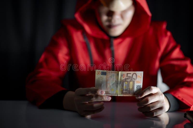 Hombre del misterio en la sudadera con capucha roja que sostiene el billete de banco euro fotografía de archivo