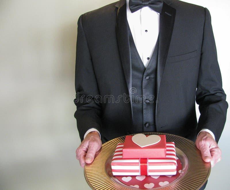 Hombre del misterio en smoking negro con los regalos del día de Valentine's foto de archivo libre de regalías