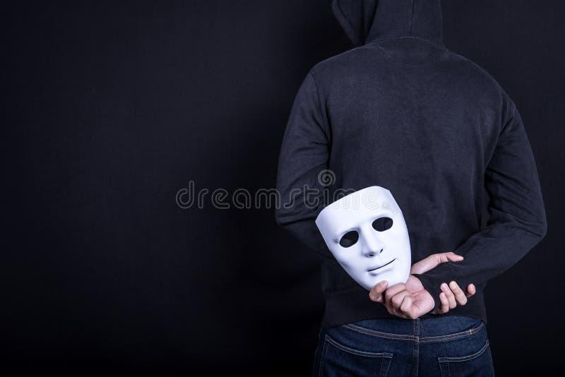 Hombre del misterio que lleva a cabo la máscara blanca en la parte posterior imagen de archivo