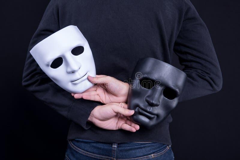 Hombre del misterio que lleva a cabo la máscara blanco y negro imagenes de archivo
