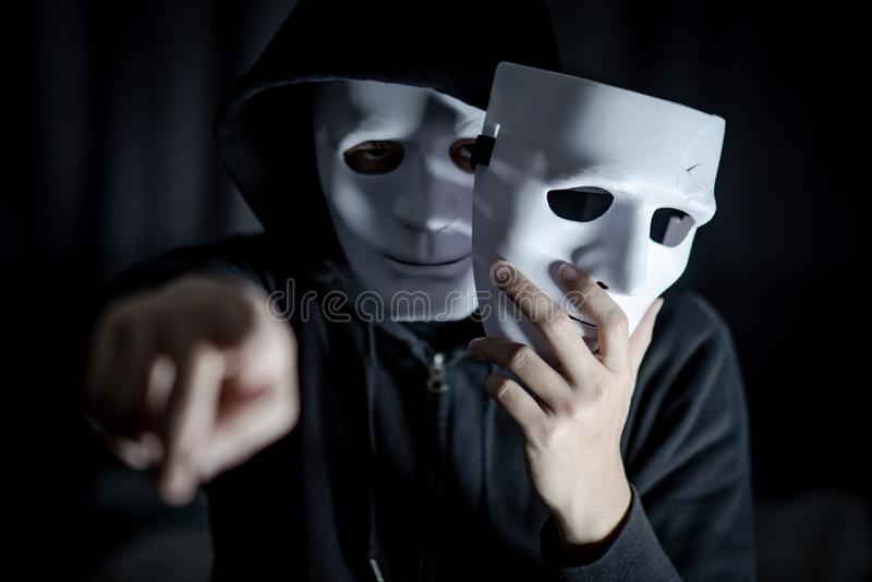 Hombre del misterio que señala y que lleva a cabo la máscara blanca fotografía de archivo
