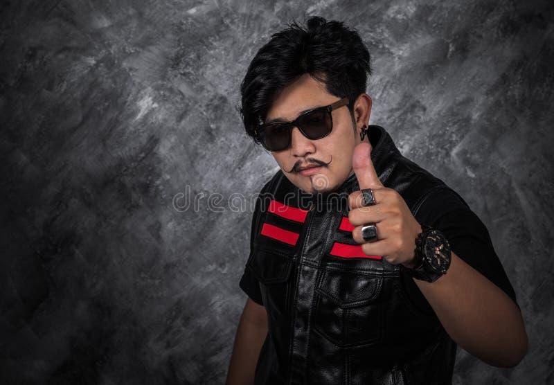 Hombre del motorista en chaqueta de cuero negra con el pulgar para arriba fotos de archivo