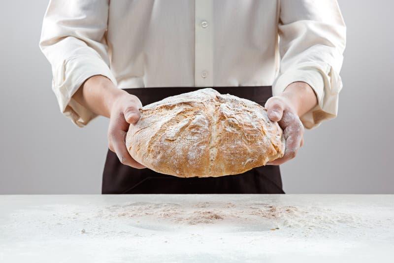 Hombre del panadero que sostiene la barra de pan orgánica rústica en manos foto de archivo libre de regalías