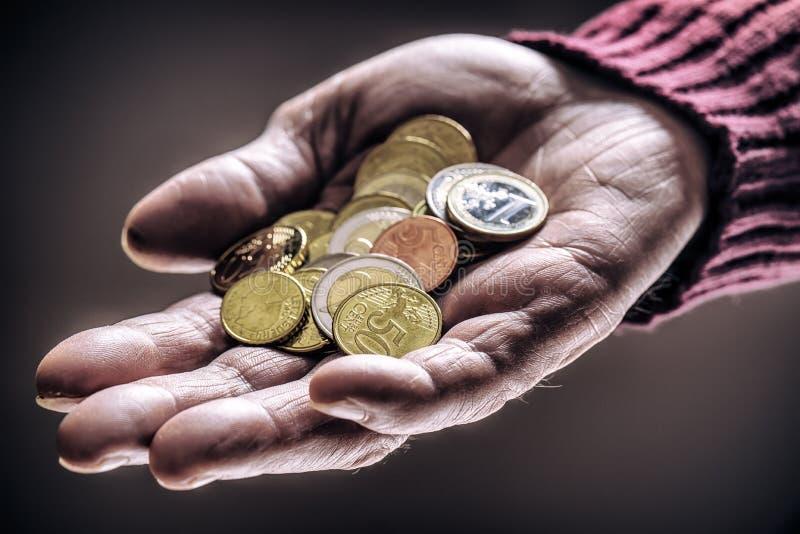 Hombre del pensionista que se sostiene en monedas del euro de las manos Tema de pensiones bajas fotos de archivo
