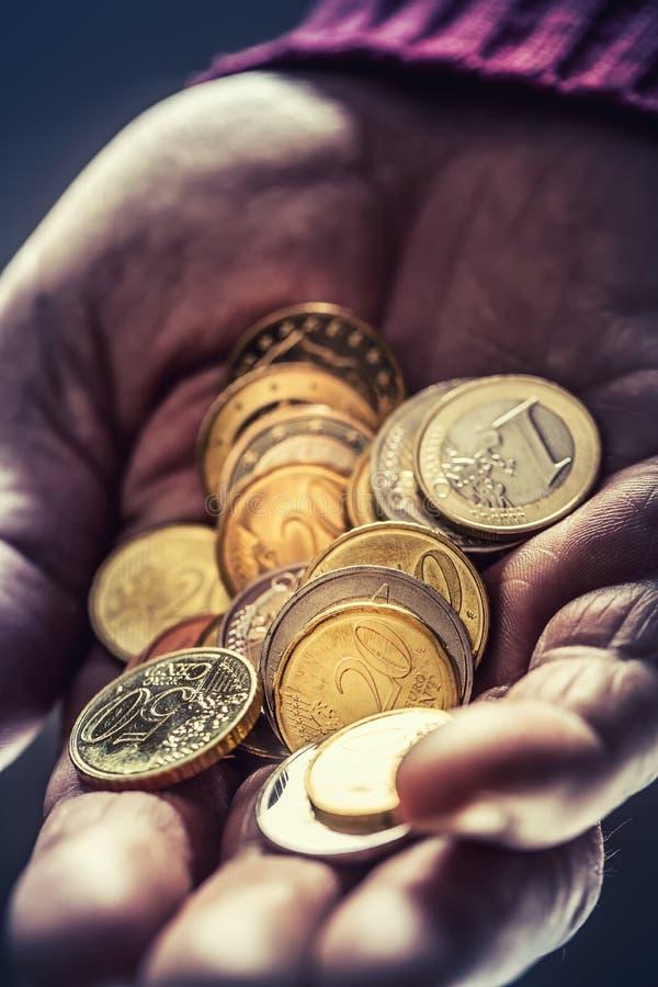 Hombre del pensionista que se sostiene en monedas del euro de las manos Tema de pensiones bajas fotos de archivo libres de regalías