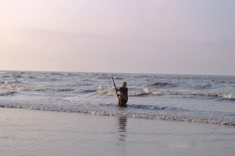 Hombre del pescador de las mujeres que pesca en el mar sagar de la isla del ganga, bahía de Bengala fotos de archivo