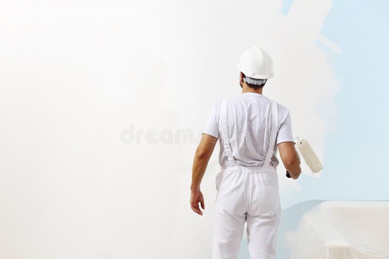 Hombre del pintor en el trabajo con un rodillo de pintura, pintura de pared fotos de archivo libres de regalías