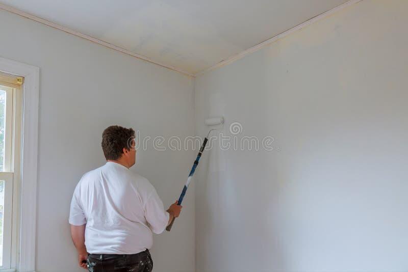 Hombre del pintor en el trabajo con un rodillo de pintura y un cubo, concepto de la pintura de pared fotografía de archivo