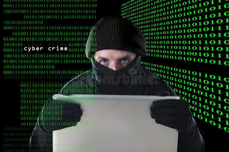 Hombre del pirata informático en negro usando el ordenador portátil del ordenador para la actividad criminal que corta contraseña imagen de archivo