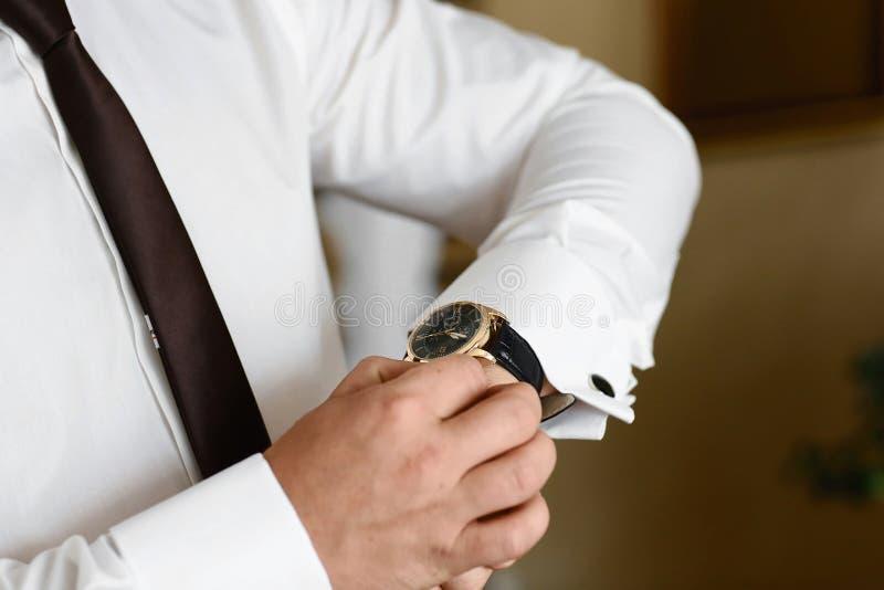 Hombre del primer que arregla sus ojales en un fondo de una camisa blanca, reloj que lleva del novio el día de boda camisa con ma fotos de archivo libres de regalías