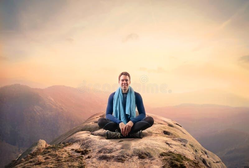 Hombre del punto que se sienta en una montaña fotografía de archivo libre de regalías