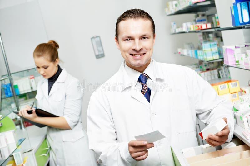 Hombre del químico de la farmacia en droguería imagen de archivo