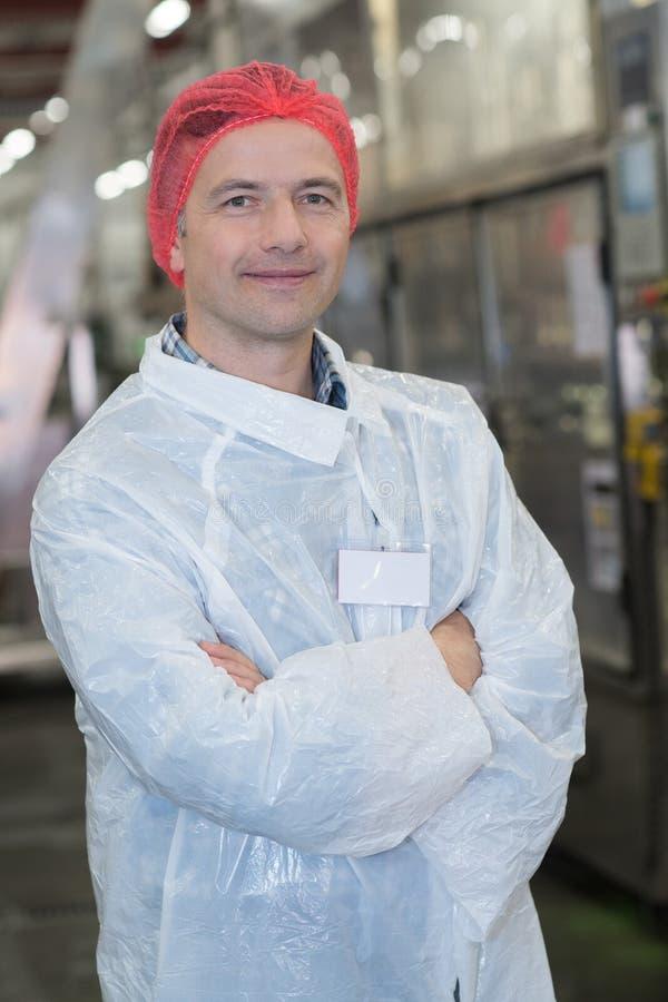 Hombre del retrato en la fábrica que lleva la ropa protectora imagenes de archivo