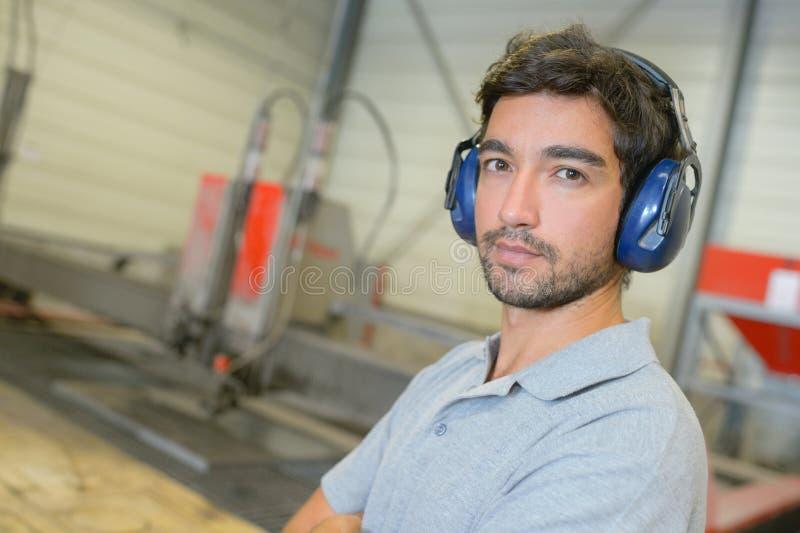 Hombre del retrato en orejeras que llevan de la fábrica imagen de archivo libre de regalías
