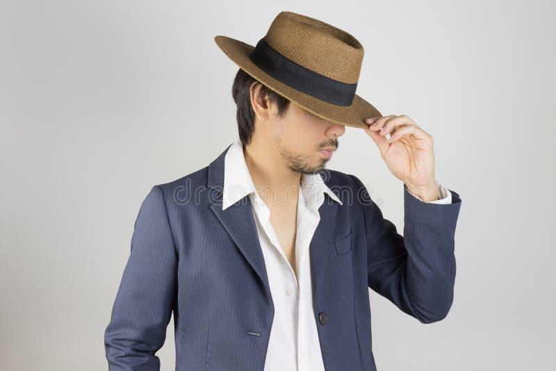 Hombre del retrato en traje de los azules marinos y moda blanca de la camisa y del sombrero en vista lateral foto de archivo libre de regalías