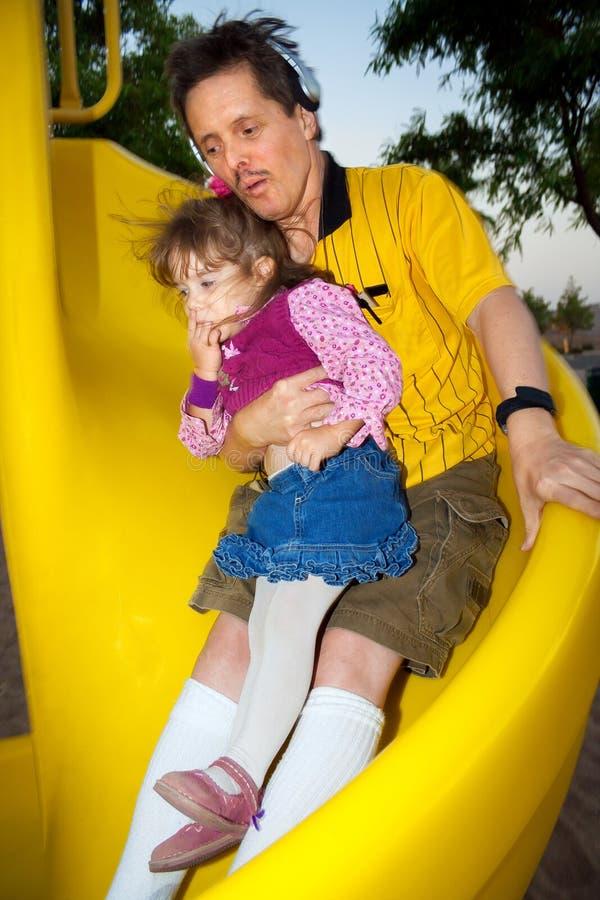 Hombre del síndrome de los plumones con la niña en su Lap Sliding Down Yell fotografía de archivo