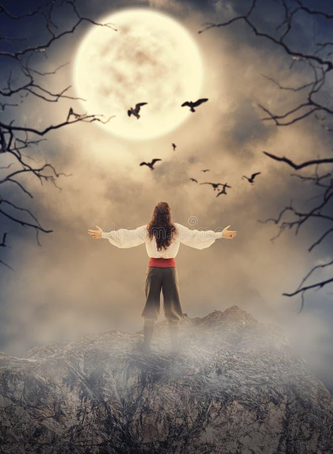 Hombre del señor que se coloca en la roca que mira en el cielo fantasmagórico Halloween s imagenes de archivo