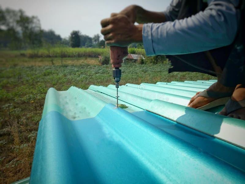 Hombre del técnico que trabaja para renovar el tejado en hogar del emplazamiento de la obra fotos de archivo libres de regalías