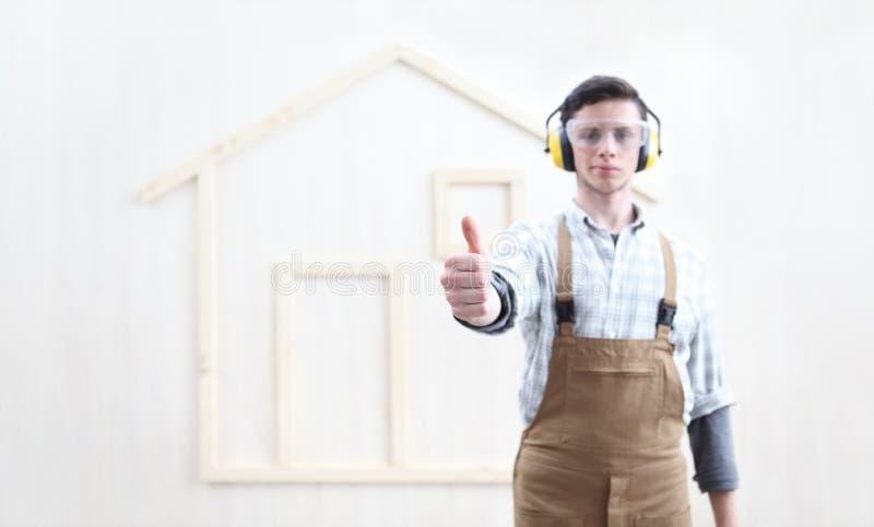 Hombre del trabajador del carpintero de la manitas del concepto de la renovación de la construcción de la casa como el pulgar de  imagen de archivo