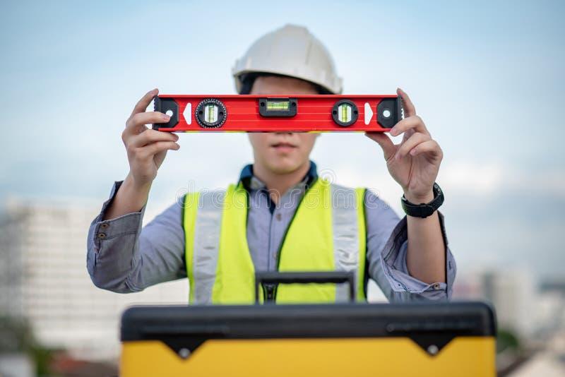 Hombre del trabajador que sostiene la herramienta de aluminio roja del nivel de alcohol foto de archivo