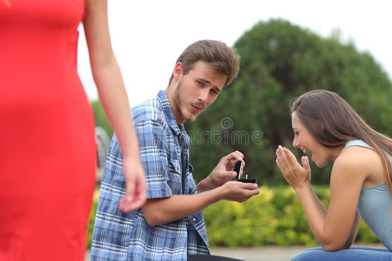 Hombre del tramposo que engaña durante una propuesta de matrimonio foto de archivo
