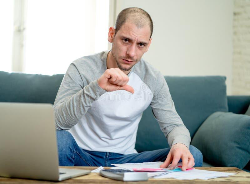 Hombre del trastorno en la tensión que paga a tarjeta de crédito deudas en línea y que cuenta finanzas con los papeles del ordena fotos de archivo