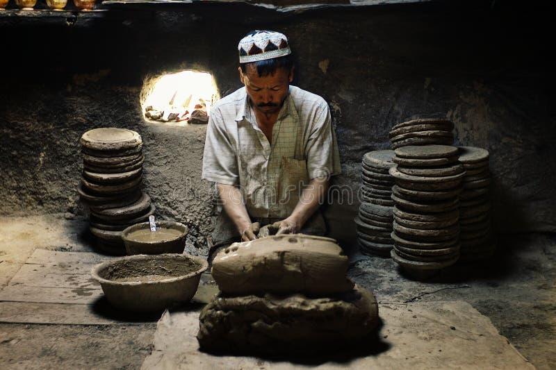 hombre del uyghur en su taller que forma la cerámica tradicional fotos de archivo