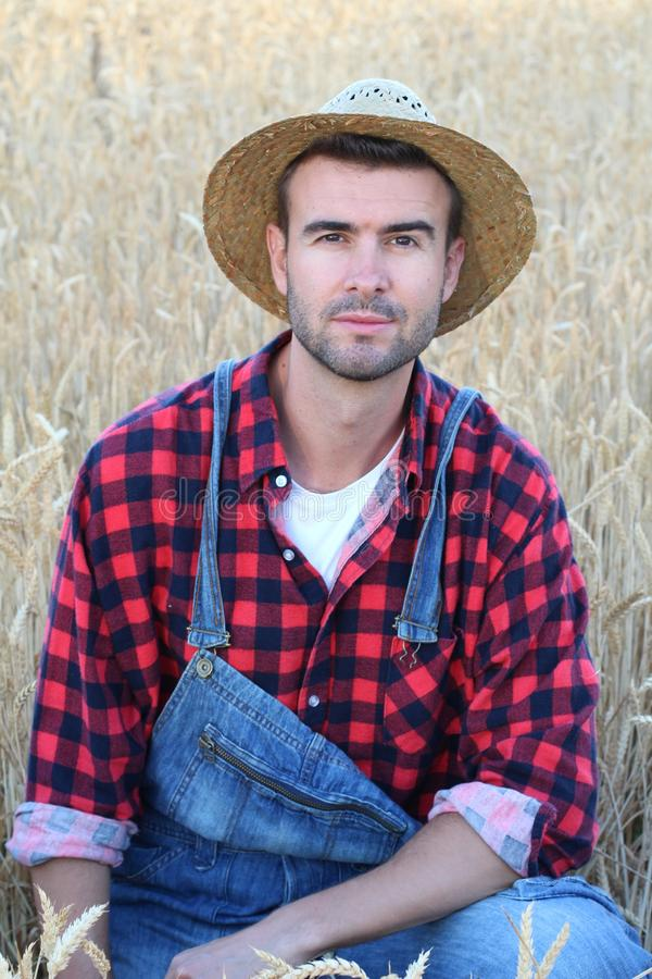 Hombre del vaquero hermoso y apuesto con el sombrero, los guardapolvos y la camisa de tela escocesa en campo rural de los E.E.U.U imagenes de archivo