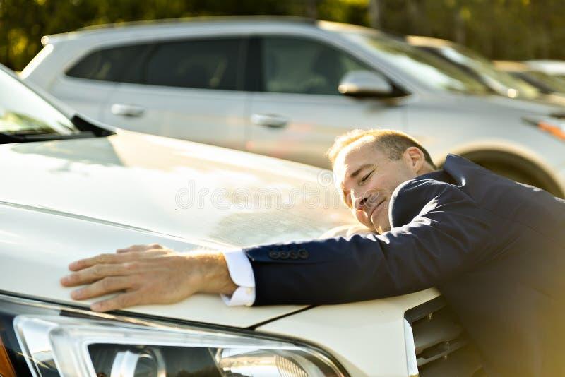 Hombre del vendedor del coche que abraza el coche en el garaje imagen de archivo