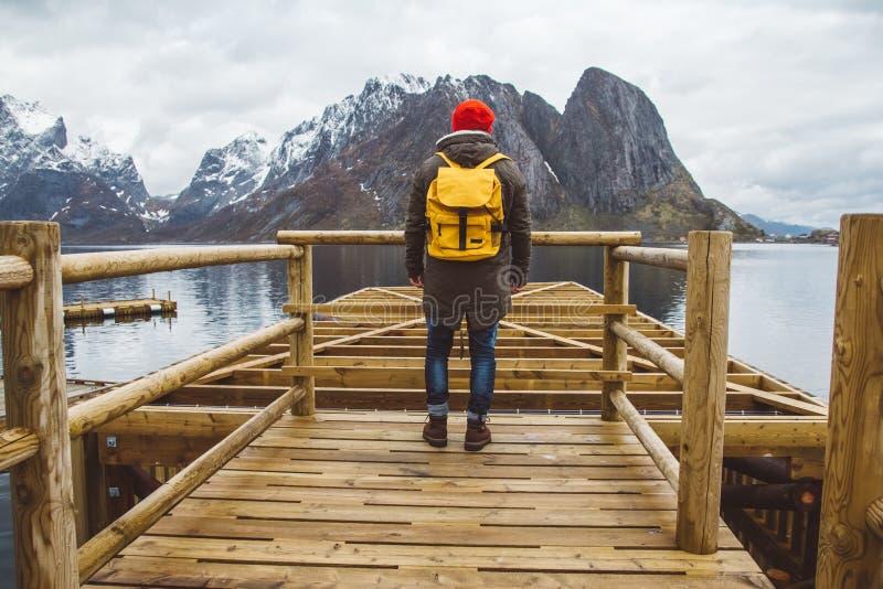 Hombre del viajero con una mochila amarilla que lleva una situaci?n roja del sombrero en el fondo de la monta?a y del embarcadero foto de archivo
