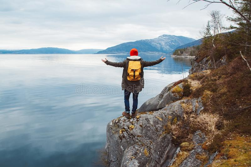 Hombre del viajero con una mochila amarilla que lleva un sombrero rojo que se coloca en las manos de una roca en el lado en el fo imagen de archivo