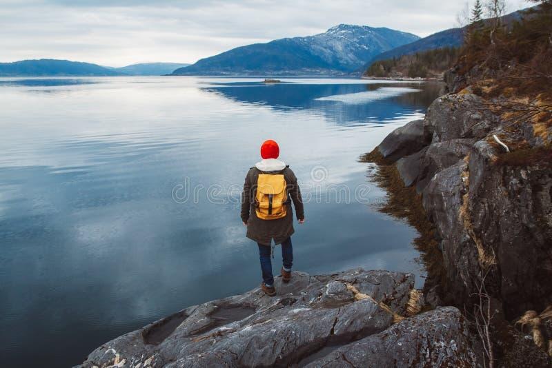 Hombre del viajero con una mochila amarilla que lleva un sombrero rojo que se coloca en una roca en el fondo de la montaña y del  fotografía de archivo