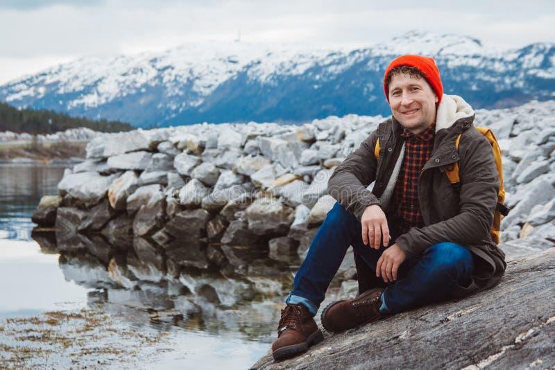 Hombre del viajero con una mochila amarilla que lleva un sombrero rojo que se sienta en la orilla en el fondo de la montaña y del fotos de archivo
