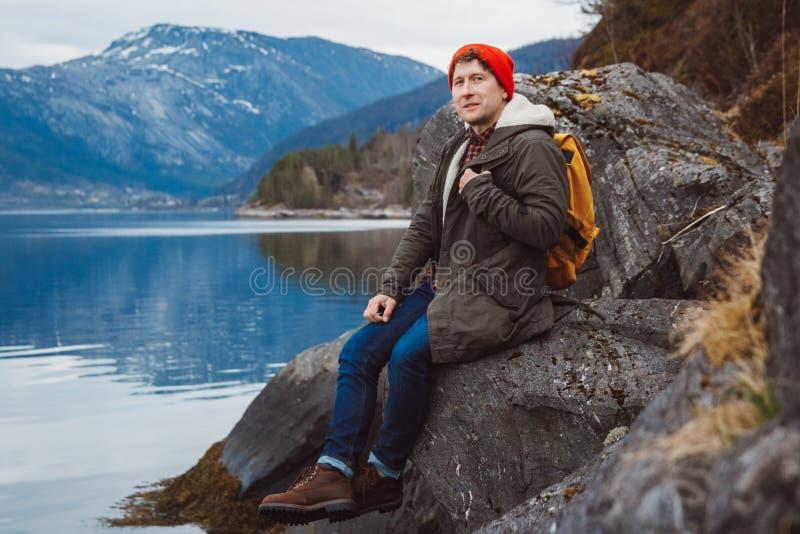 Hombre del viajero con una mochila amarilla que lleva un sombrero rojo que se sienta en la orilla en el fondo de la montaña y del imágenes de archivo libres de regalías