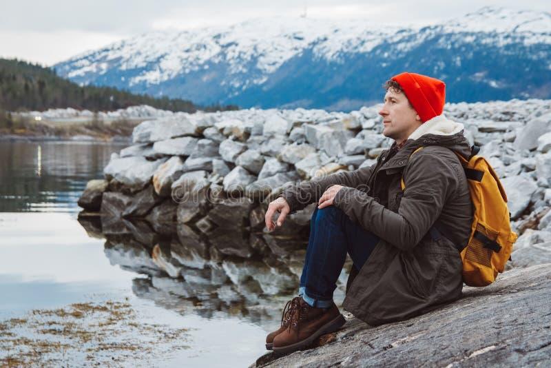 Hombre del viajero con una mochila amarilla que lleva un sombrero rojo que se sienta en la orilla en el fondo de la montaña y del foto de archivo libre de regalías