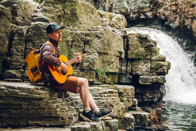 Hombre del viajero con una mochila que toca la guitarra contra una cascada Espacio para su mensaje de texto o contenido promocion foto de archivo