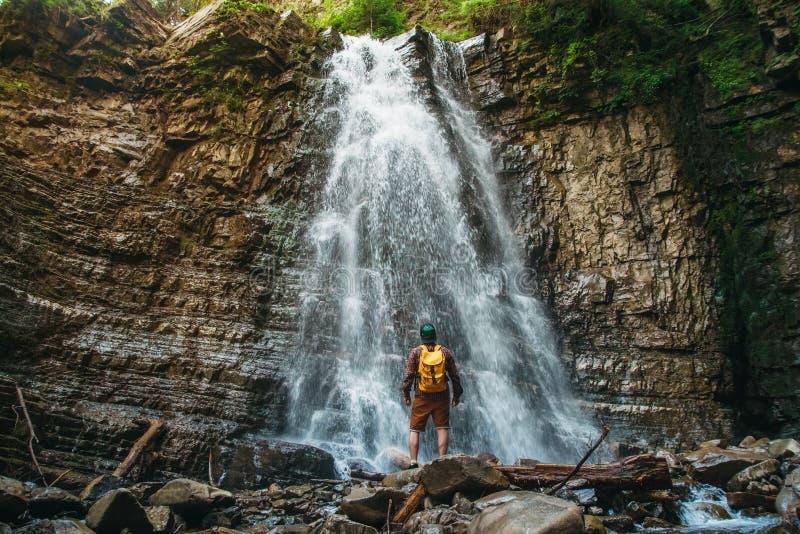 Hombre del viajero con una situación amarilla de la mochila en el fondo de una cascada Concepto de la forma de vida del viaje imagenes de archivo