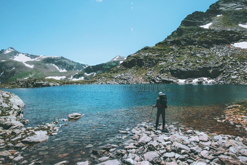 Hombre del viajero que se coloca en el lago azul en la forma de vida del viaje de las montañas que camina verano del concepto de  foto de archivo