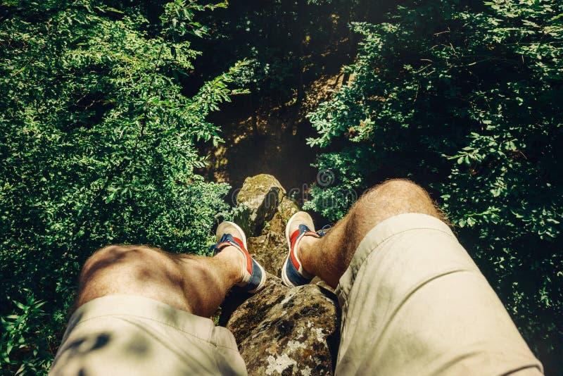 Hombre del viajero que se sienta encima de la roca sobre el bosque del verano, tiro de Point of View fotografía de archivo libre de regalías