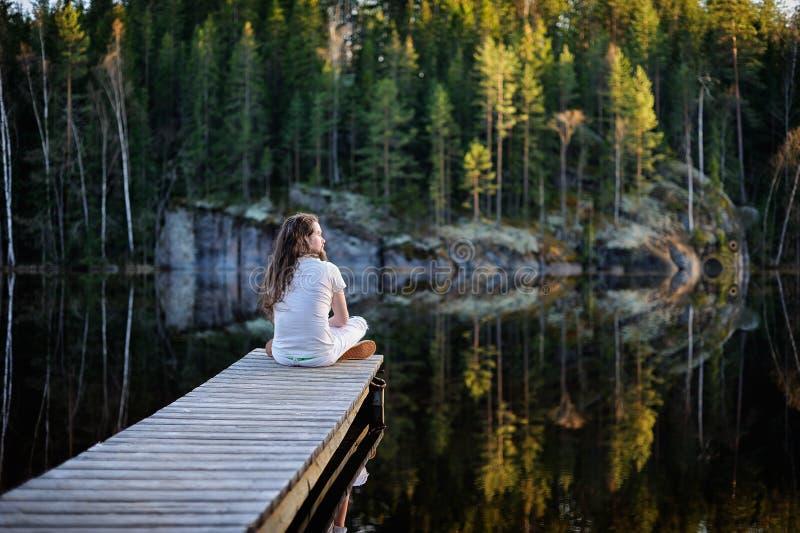 Hombre del viajero que se sienta por un lago imagenes de archivo