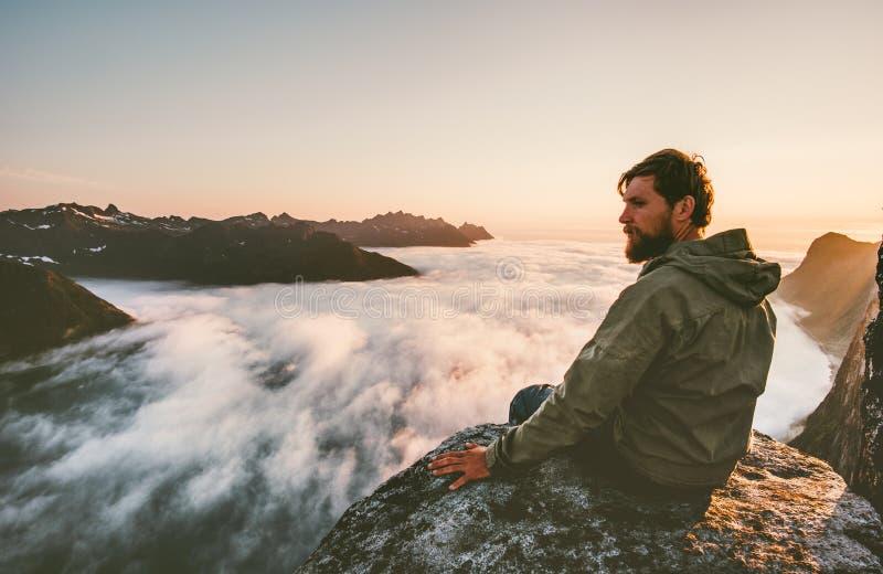 Hombre del viajero que se sienta solamente en las montañas del acantilado del borde sobre las nubes imágenes de archivo libres de regalías