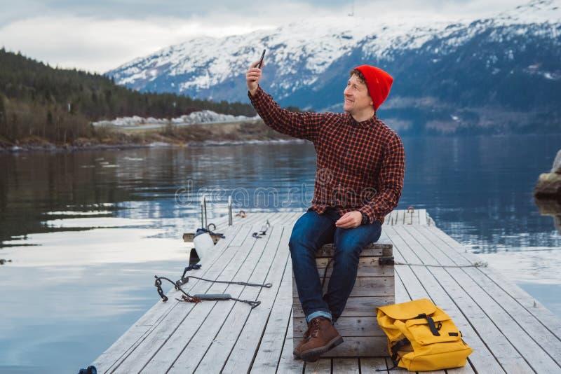 Hombre del viajero que toma a autorretrato una foto con un smartphone Turista en una mochila amarilla que se sienta en el embarca fotografía de archivo libre de regalías