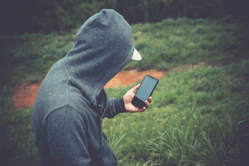 Hombre del viajero que usa el teléfono móvil en la montaña foto de archivo libre de regalías