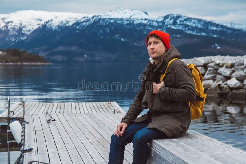 Hombre del viajero del retrato con una mochila amarilla que lleva un sombrero rojo que se sienta en el embarcadero de madera en e foto de archivo libre de regalías